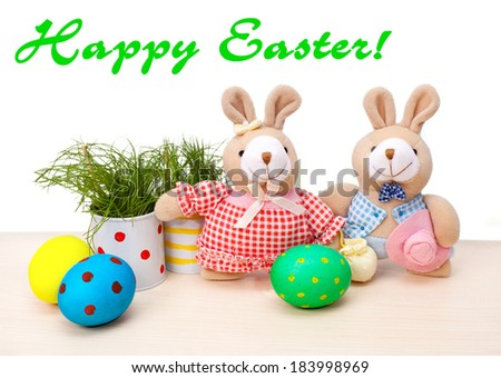Easter eggs with teddy rabbits and grass - stock photo
