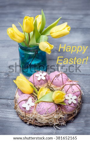 Easter eggs with yellow tulips in vase, shot from the top