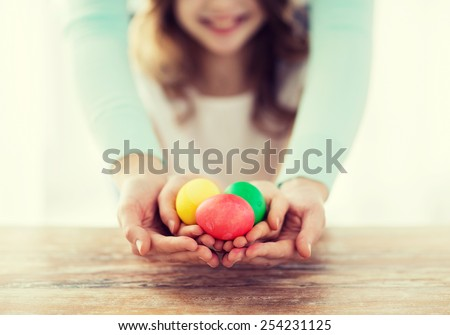 easter, family, holiday and child concept - close up of little girl and mother holding colored eggs - stock photo