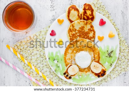 Easter funny bunny pancakes with fruit. Creative breakfast for kids of pancakes, kiwi, banana, apple and juice on a white background top view - stock photo