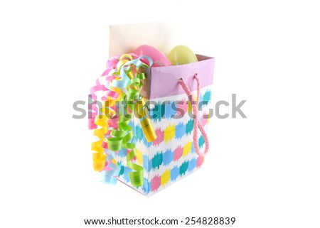 Easter gift bag with gift card, eggs, and ribbon. - stock photo