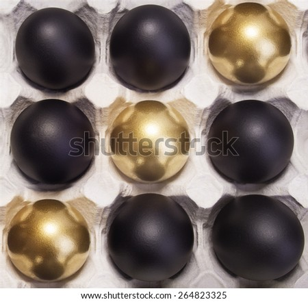 Easter gold and black eggs in container - stock photo