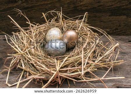 Easter golden and silver eggs on the nest with wooden background