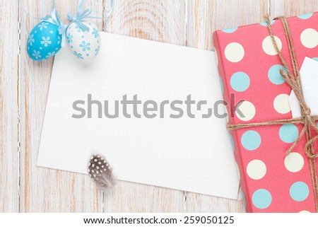 Easter greeting card with blue and white eggs and gift box over white wood. Top view with copy space - stock photo