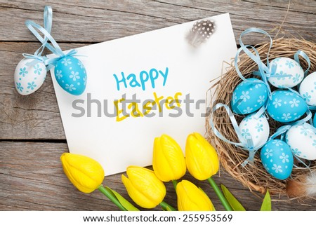 Easter greeting card with blue and white eggs and yellow tulips over wood. Top view with copy space - stock photo