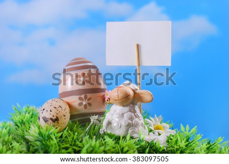 easter greeting card with cute lamb figurine and eggs on the grass against blue sky - stock photo