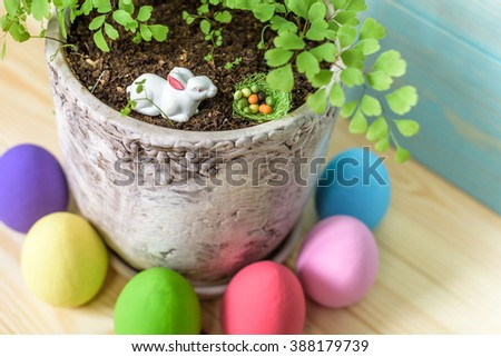 Easter greeting card with easter bunny, grass and eggs in nest concept macro - stock photo