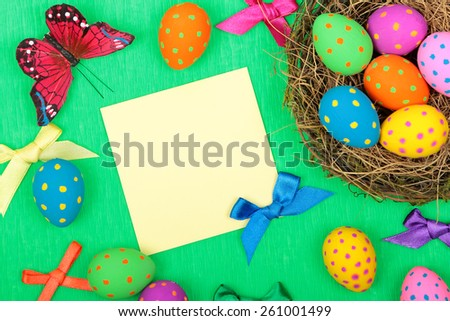 Easter greeting card with eggs, bows and butterfly on green background - stock photo