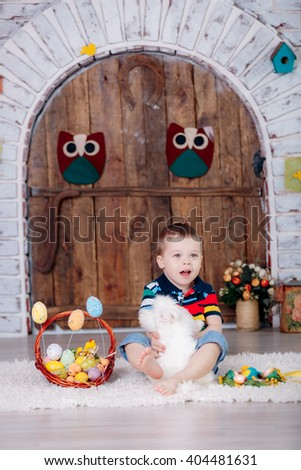 easter, happy boy with white rabbit on hands and easter eggs. - stock photo