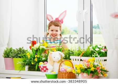 Easter. happy child girl with bunny ears and colorful eggs sitting at the window of a house in flowers
