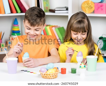Easter holiday - cute children coloring eggs for easter at home - stock photo