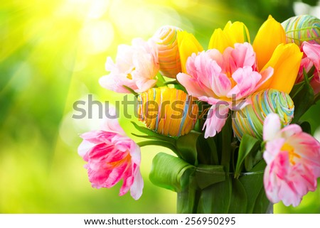 Easter Holiday flowers bunch with colourful eggs . Beautiful Colorful tulips flowers bouquet decorated with painted handmade eggs. Happy Easter art design. Springtime, Sunflare - stock photo
