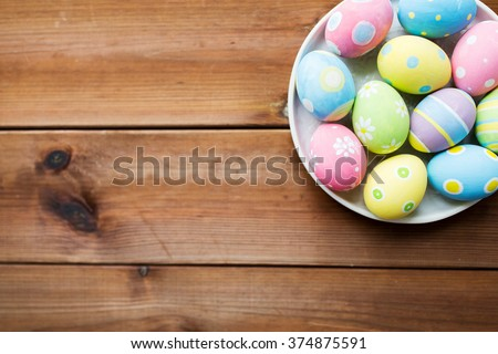 easter, holidays, tradition, advertisement and object concept - close up of colored easter eggs on plate - stock photo