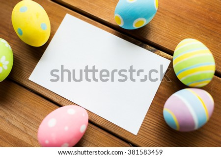 easter, holidays, tradition and object concept - close up of colored easter eggs and blank white paper card on wooden surface with copy space - stock photo