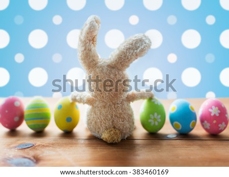 easter, holidays, tradition and object concept - close up of colored easter eggs and bunny over blue polka dot background - stock photo