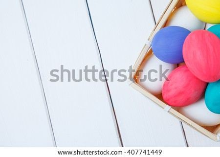 Easter, holidays, tradition and object concept - close up of colored easter eggs in basket - stock photo