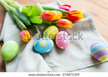easter, holidays, tradition and object concept - close up of colored easter eggs in basket and tulip flowers - stock photo