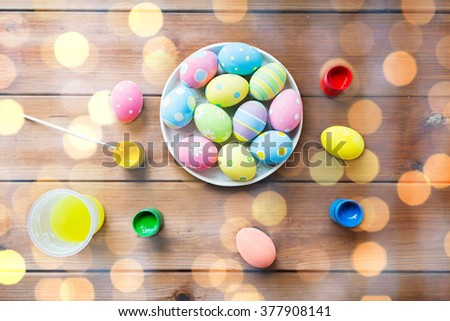 easter, holidays, tradition and object concept - close up of colored easter eggs on plate - stock photo