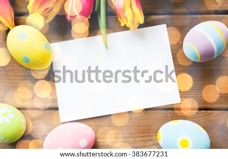 easter, holidays, tradition and object concept - close up of colored easter eggs, tulip flowers and blank white paper card on wooden surface with copy space over holidays lights - stock photo