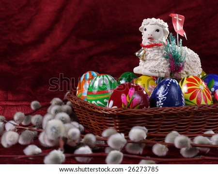 Easter Lamb figurine on painted Easter eggs put in wicker basket and bunch of pussy willow branches