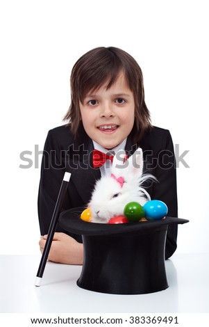 Easter magic - boy pulling a grumpy rabbit and colorful eggs from the magician hat - stock photo