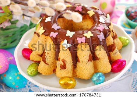 easter marble ring cake with butterfly sprinkles and poured chocolate sauce - stock photo