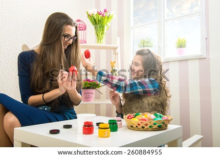 Easter - Mother and daughter painted with egg - stock photo