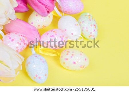 Easter multicolored tulips and eggs on yellow paper - stock photo