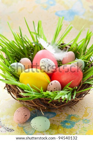Easter nest with colored and chocolate eggs - stock photo