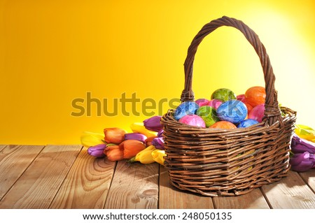 Easter nest with colored hen's eggs tulip in front of orange background on wooden board - stock photo