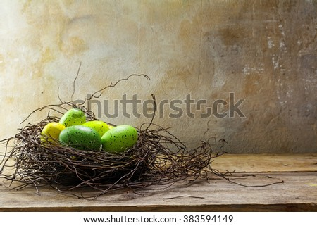 Easter nest with green colored eggs on rustic wood planks against a rural vintage wall with copy space in the background, selected focus, narrow depth of field - stock photo