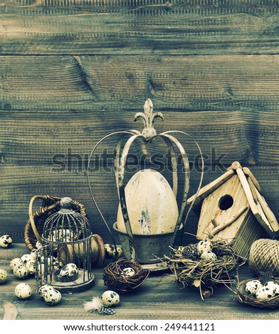 Easter nostalgic home decoration. Still life with eggs, nest and birdcage. Retro style dark toned picture - stock photo