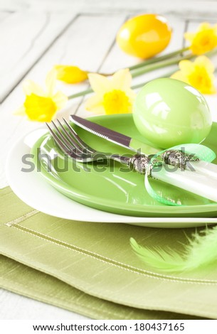 Easter or spring white dinner table setting with fresh daffodil flowers and pastel green decorations. Elegant plates and cutlery.