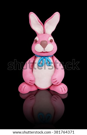 Easter pink plasticine bunny rabbit on a black mirror background