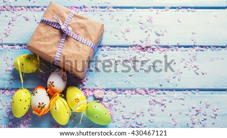 Easter postcard. Box with present,  bright Easter eggs on blue wooden background. Selective focus. Place for text. Toned image. - stock photo