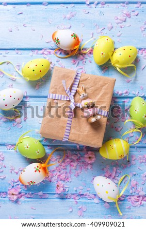 Easter postcard. Box with present, decorative rabbit, bright Easter eggs on blue wooden background. Selective focus.