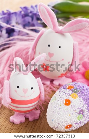 Easter rabbit egg decoration with flower and feather - stock photo