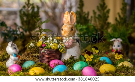 Easter rabbit figurines with colorful eggs on moss.
