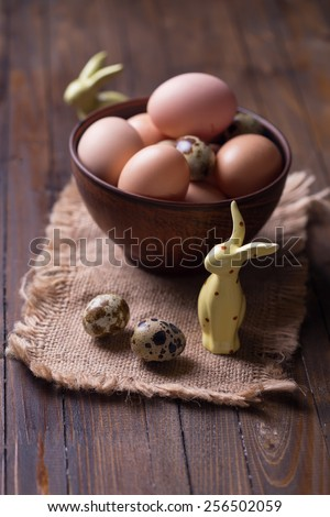 Easter rabbits, chicken and quail eggs on wooden background. Selective focus. - stock photo