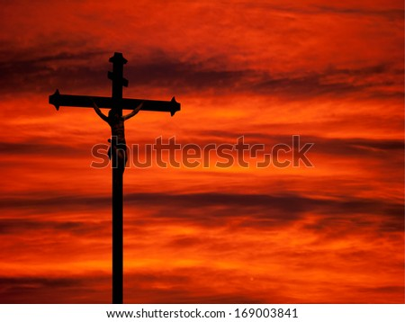 Easter religious background - church statue against red sunset sky. - stock photo