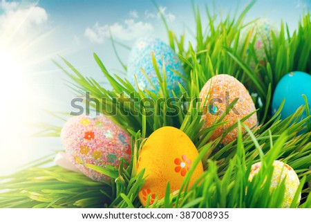 Easter scene background. Beautiful colorful eggs in spring grass meadow over blue sky with sun border design - stock photo