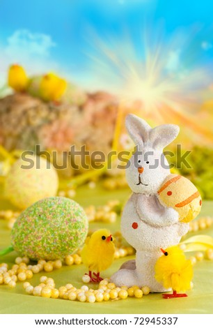 Easter setting with Easter eggs, chicks and rabbit and blue sky in the back.