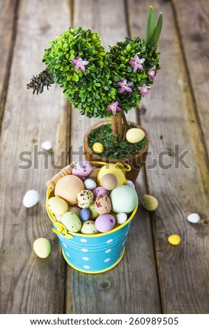 Easter setup of pastel colored eggs in decorative blue polka dot bucket and bird shaped blooming tree on grunge style wooden table - stock photo