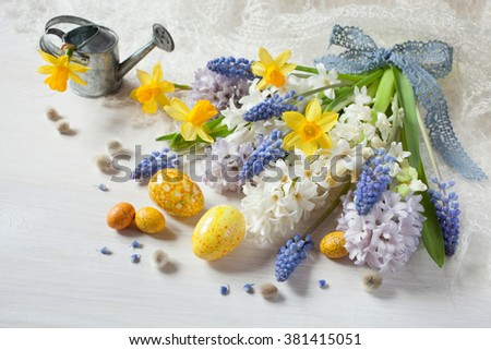 Easter spring flowers hyacinths, daffodils and eggs on a wooden table - stock photo