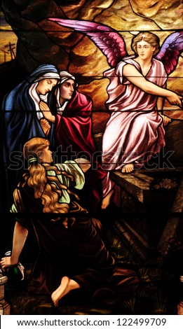 Easter stained glass window depicting Mary Magdalen and women at the empty tomb of Jesus on day of Resurrection - stock photo