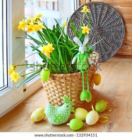 Easter still life with a happy rabbit, chicken and easter eggs in the yellow daffodils in a basket - stock photo