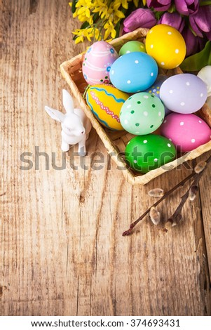 Easter still life with basket eggs rabbit and bunch spring flowers on wooden board - stock photo