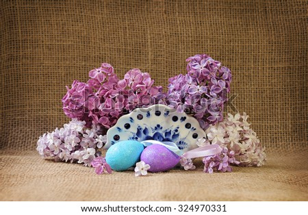 Easter still life with beautiful flowers of lilac and easter eggs. Rustic style. - stock photo