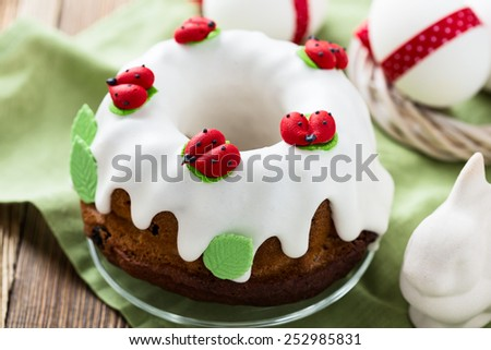 Easter sweet ring cake with glace icing decoration and white easter eggs with red bow on rustic wooden table - stock photo