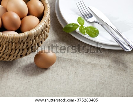 Easter table. Basket with eggs, white plates with silver cuttle ry - stock photo